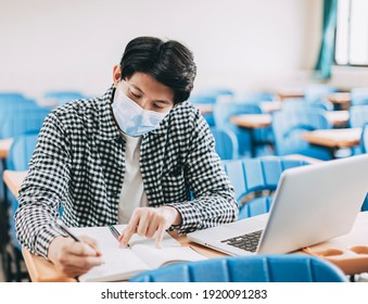young  student wearing face mask and studying in  classroom