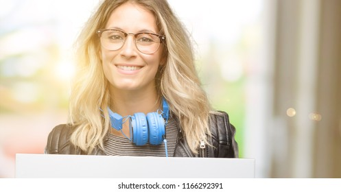 Young student woman with headphones holding blank advertising banner, good poster for ad, offer or announcement, big paper billboard