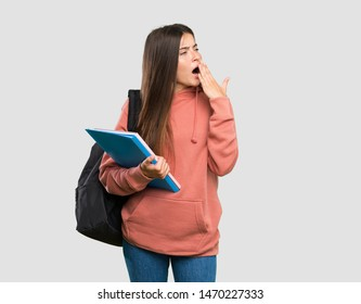 Young student woman holding notebooks yawning and covering wide open mouth with hand over isolated grey background