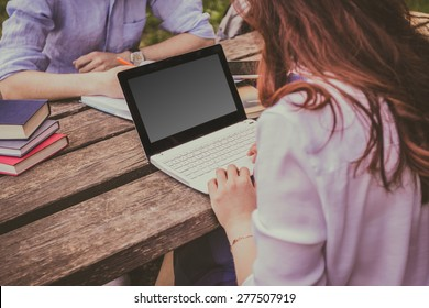 Young student woman taping on laptop in a city park on a wooden table and a young student man writing in a journal.Young student outdoors with laptop and tablet.Life style.City