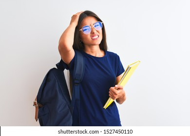 Young student woman wearing backpack glasses holding book over isolated white background stressed with hand on head, shocked with shame and surprise face, angry and frustrated. Fear and upset