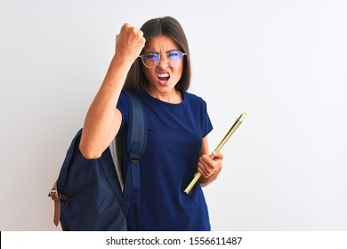 Young student woman wearing backpack glasses holding book over isolated white background annoyed and frustrated shouting with anger, crazy and yelling with raised hand, anger concept