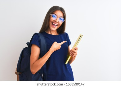 Young student woman wearing backpack glasses holding book over isolated white background very happy pointing with hand and finger