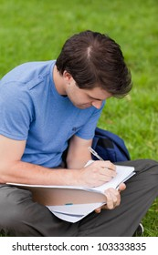 Young student working with his notebook while sitting on the grass