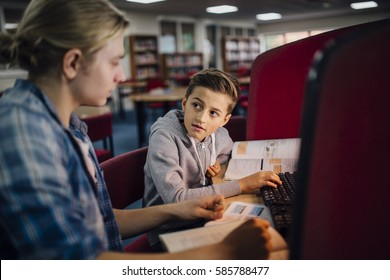 Young student is working with an older student to catch up with work. They are talking and discussing something in the textbook and the little boy is typing on the computer