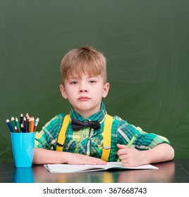 Young student writes in a notebook near empty green chalkboard