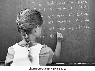 young student writing lines on a school chalkboard