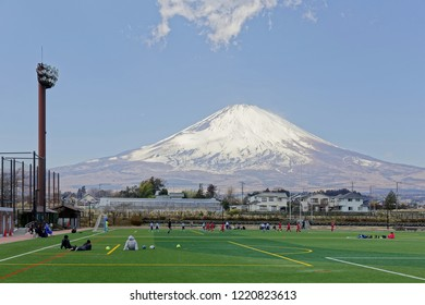 Young student-athletes exercising on a soccer field with the majestic snow capped Mount Fuji under blue sky in background on a sunny winter day, in the rural countryside of Gotenba, Shizuoka, Japan