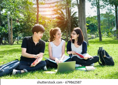 Young students asian together group teenager smile with laptop computer, school folders reading book at high school university campus college knowledge center for study learning in summer outdoor.
