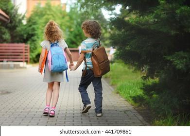 Junge Schüler, Junge und Mädchen, gehen zur Schule. Sie halten Hände. Sie halten Hände. Kinder hinter den Schultern haben Schultern. Warmer Tag im Frühherbst.