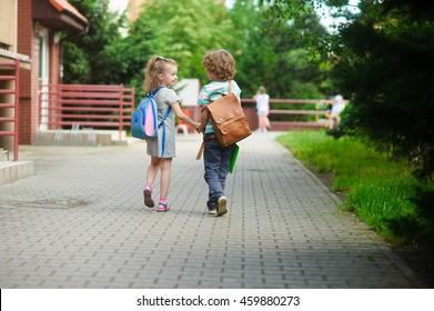 Junge Schüler, Junge und Mädchen, gehen zur Schule. Sie halten Hände. Sie halten Hände. Kinder hinter den Schultern haben Schultern. Warmer Tag im Frühherbst.Zurück zur Schule.