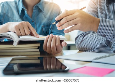 Young students campus helps friend catching up and learning tutoring. People, learning, education and school concept. - Shutterstock ID 655037578