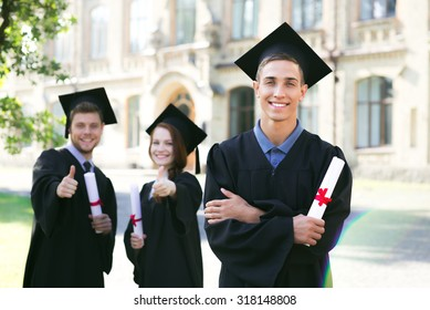 Young students dressed in black graduation gown. Campus as a background. Boy cheerfully smiling, holding diploma and looking at camera. Focus on one student. Boy and girl are on background