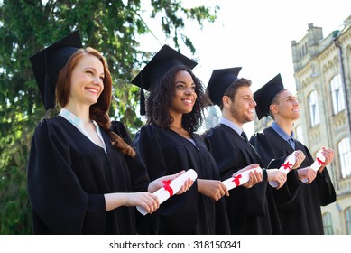 Young students dressed in black graduation gown. Campus as a background. Students standing in row, cheerfully smiling, holding diplomas and looking straight ahead