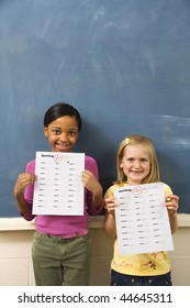 Young students holding spelling tests with good grades. Vertically framed shot.