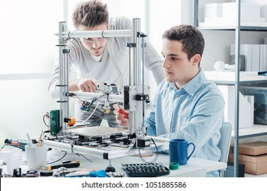 Young students in the laboratory using a 3D printer, technology and education concept