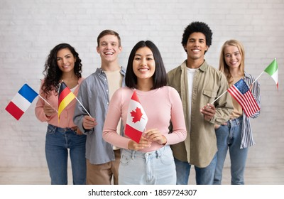 Young students of language school celebrate holiday. Happy millennial peoples of different nationalities have fun on study and hold little flags on brick white wall background, studio shot, free space