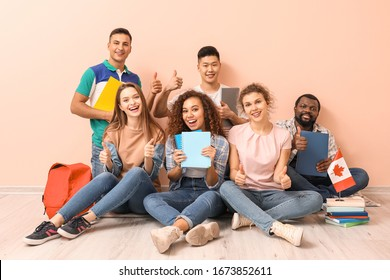 Young students of language school sitting near color wall