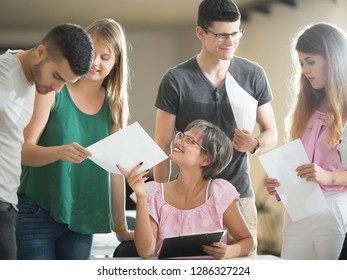 Young students and professor holding paper