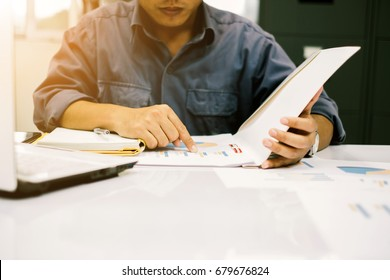 Young students sit down to research and write down statistical information to gather results summarize the book to graduate report over blurred library. select focus and Film Tone with Light fair