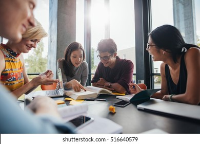 Young students sitting at a table in a library and reading books for their class assignment. University students doing group study in library.