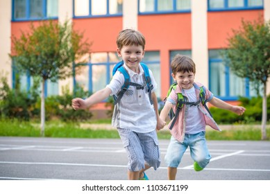 Young students, two sibling brothers, going to school. They hold hands. Children behind shoulders have satchels. Warm day in an early autumn. Back to school. Happy smiling kids.