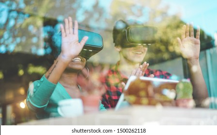 Young students using virtual reality goggles in modern coworking bar - Window reflection view - Millennials people having fun with vr technology - Future and digital concept - Focus on girl headset