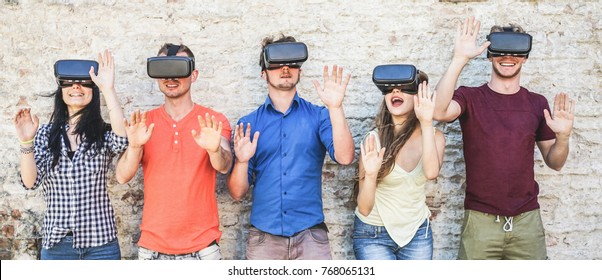 Young students wearing virtual reality glasses outdoor - Happy people having fun with new technology vr headset goggles - New generation mania trends concept - Warm filter