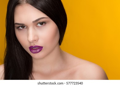 Young stunner. Studio portrait of a gorgeous young brunette looking fiercely to the camera wearing purple lipstick and golden eyeliner posing on yellow background creative colorful makeup concept