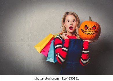 Young style girl in jeans clothes with shopping bags and halloween pumpkin on grey background.