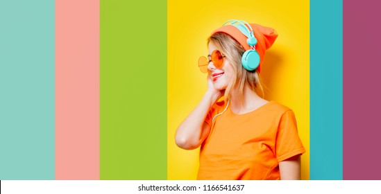 Young style girl with orange glasses and headphones on color background. Clothes in 1980s style