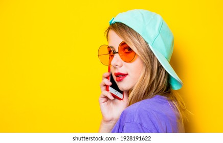 Young style girl with orange glasses with her phone on yellow background. Clothes in 1980s style