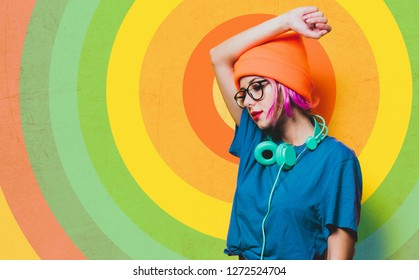 Young style girl in purple clothes with headphones on yellow background.  Clothes in 1980s style