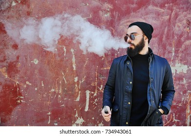 Young stylish bearded man in a black hat with an electronic cigarette or vape