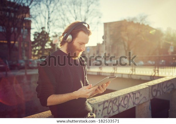 young stylish bearded man listening to music in the city