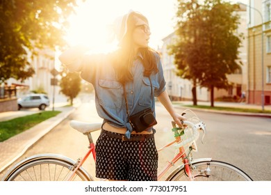 Young stylish beautiful cute woman in white hat posing in summer evening on the street with vintage bicycle