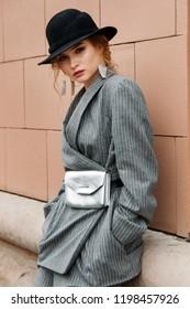 young stylish beautiful woman fashion model is posing in street, wearing pantsuit, having purse on her waist