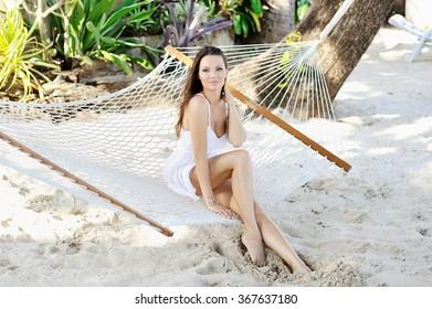 Young stylish beautiful woman posing in hammock