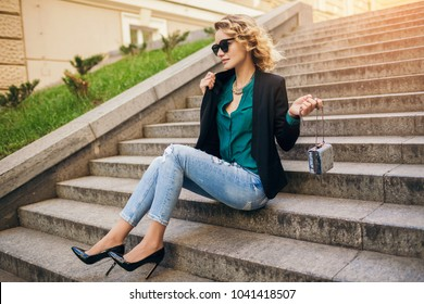 young stylish beautiful woman sitting in street, wearing jeans, black jacket, green blouse, sunglasses, holding purse, elegant style, summer fashion trend, legs details, high heeled shoes, footwear