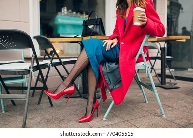 young stylish beautiful woman sitting in city cafe in red coat, street style, autumn trend, warm clothes, drinking coffee, elegant, high heeled shoes, sexy, tights, accessories, slim legs detail