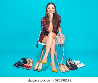 young stylish beautiful woman in trendy dress sitting on blue studio background surrounded with different pairs of fashionable shoes, summer fashion trend footwear, shopping, legs, fitting heels