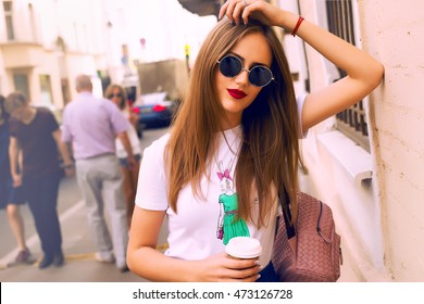 young stylish beautiful woman walking on city street on sunset, europe vacation, holding cup of her hot coffee,Autumn trend,sunglasses, smiling, luxury, red lips, fashionable outfit, denim outfit