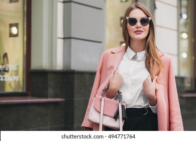 young stylish beautiful woman walking in street, wearing pink coat, purse, sunglasses, white shirt, black skirt, fashion outfit, autumn trend, smiling happy, accessories