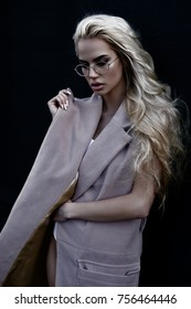 Young stylish blonde girl in modern sunglasses posing for camera in beauty and in steetstyle in pink coat without sleeves and with white body