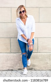 young stylish blonde girl in white blouse and blue jeans posing near wall