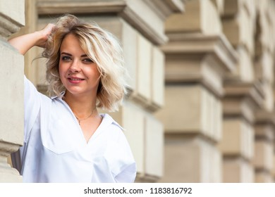 young stylish blonde girl in white blouse posing near wall