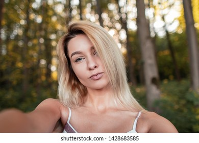Young stylish blonde woman in a striped pink fashionable sundress makes selfie standing in the forest on a bright sunny summer day. Cute girl with blue eyes is taking a picture of herself.