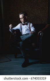 A young stylish boy with a watch in his hands in a shirt, trousers, suspenders and glasses sits on a leather armchair