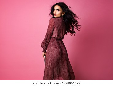 young stylish brunette woman with curly long hair in female casual dress is standing from the back with book in hands and looking straight on the pink wall background, fashion concept, free space