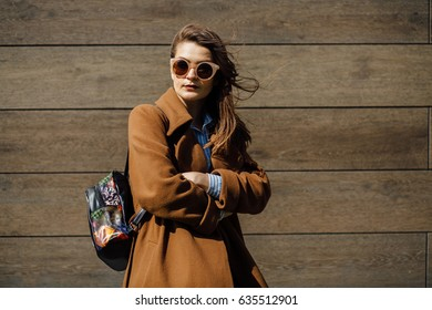 Young stylish brunette woman student wrapping up in brown coat over wooden texture wall in spring windy sunny day.